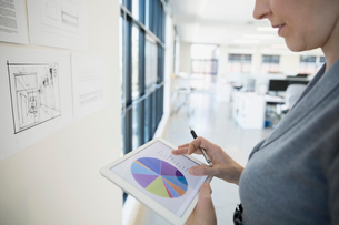 Businesswoman reviewing pie chart on digital tablet officeの写真素材 [FYI02285308]