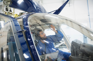 Mechanic checking instruments in helicopter cockpitの写真素材 [FYI02285500]