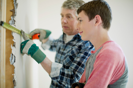 father and teenage son doing home renovationsの写真素材 [FYI02285547]