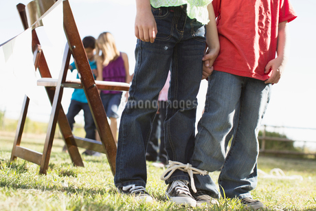 Kids getting ready to compete in a 3 legged race.の写真素材 [FYI02285561]