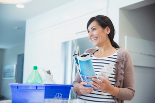 Happy mid adult woman with recyclable materials and bin looking awayの写真素材 [FYI02285571]