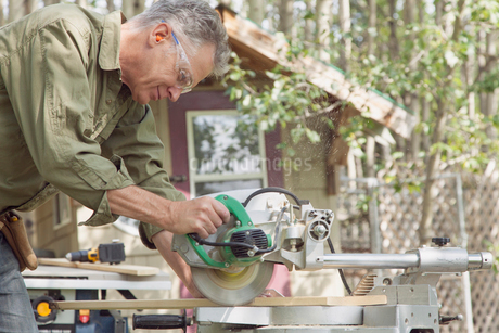 middle-aged man using power saw to cut plank of woodの写真素材 [FYI02285580]