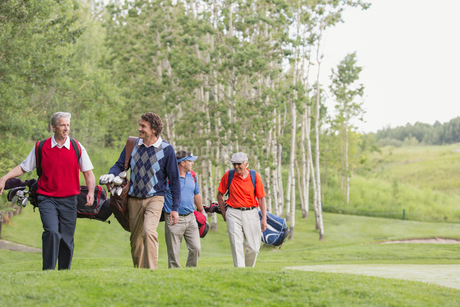 foursome of golfers walking on fairwayの写真素材 [FYI02285606]