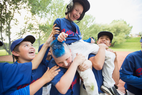 boys baseball team giving teammate a shoulder rideの写真素材 [FYI02285669]