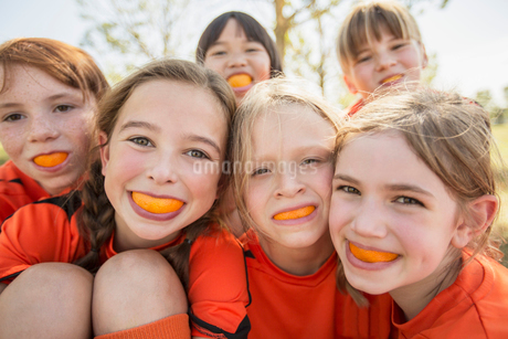 soccer girls making faces with orangesの写真素材 [FYI02285686]