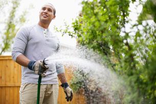 young adult man watering gardenの写真素材 [FYI02285725]