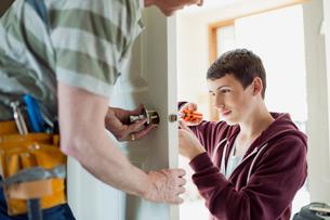 father and teenage son replacing door lockの写真素材 [FYI02285729]