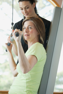 trainer assisting woman with weight trainingの写真素材 [FYI02285749]