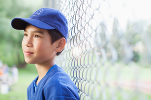 young male baseball player standing by fenceの写真素材 [FYI02285753]