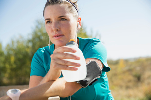 Woman stopping to drink water during outdoor workout.の写真素材 [FYI02285754]