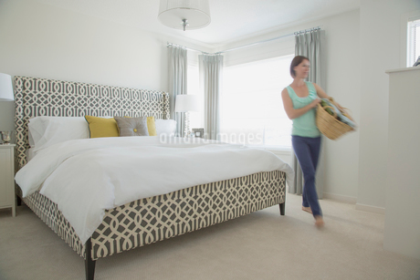 Mid-adult woman with laundry basket in modern bedroom.の写真素材 [FYI02285775]