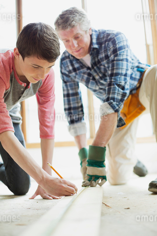father and teenage son doing home renovationsの写真素材 [FYI02285800]