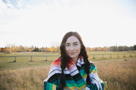 Portrait brunette young woman wrapped in a blanket in fieldの写真素材 [FYI02285803]