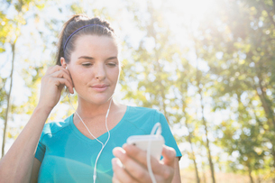 Woman using music player during outdoor workout.の写真素材 [FYI02285828]