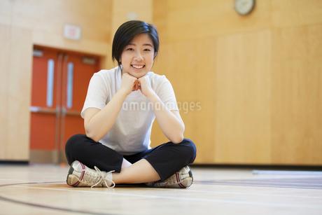 Portrait of Asian, middle school student sitting on gym floor.の写真素材 [FYI02285861]