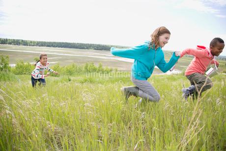 elementary aged children running in grasslandの写真素材 [FYI02285865]