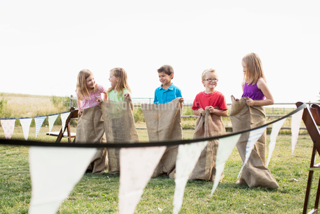 Kids lined up to start a potato sack race.の写真素材 [FYI02285960]