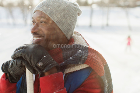 Thoughtful mid adult man smiling in snowの写真素材 [FYI02285995]