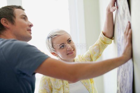 mid adult couple holding up wallpaper to viewの写真素材 [FYI02286049]
