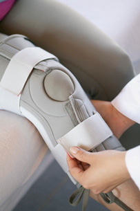 doctor fastening knee brace on patientの写真素材 [FYI02286089]