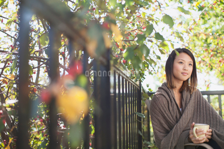 Thoughtful young woman wrapped in blanket holding coffee outdoorsの写真素材 [FYI02286107]