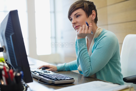 Businesswoman working on computer at office deskの写真素材 [FYI02286156]