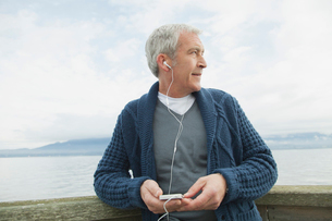 Profile of middle-aged man on dock listening to music.の写真素材 [FYI02286166]