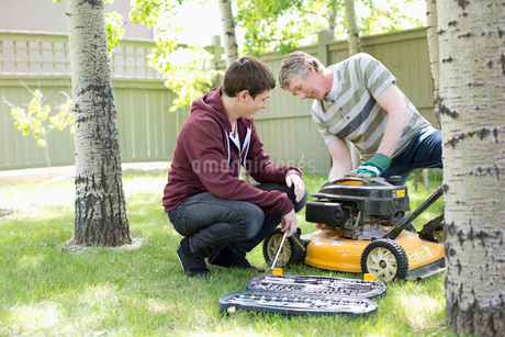 father and son maintaining lawn mowerの写真素材 [FYI02286173]