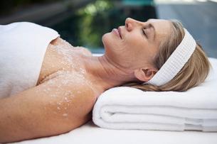 middle aged woman having salt scrub treatmentの写真素材 [FYI02286230]
