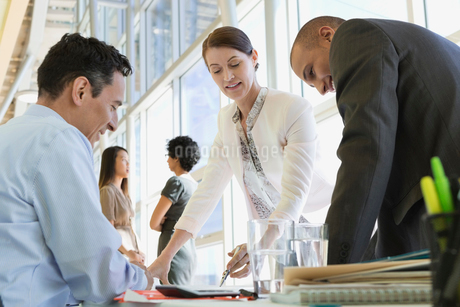 Businesswoman reviewing paperwork with male colleaguesの写真素材 [FYI02286281]