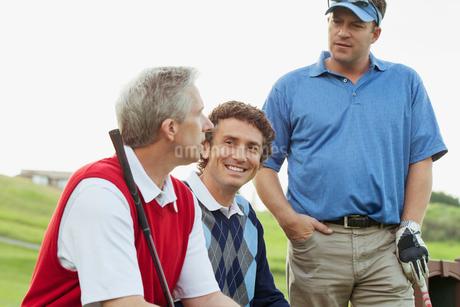 golfers sitting on bench having a conversationの写真素材 [FYI02286317]