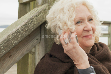 Senior woman having a conversation outdoors on cell phone.の写真素材 [FYI02286463]