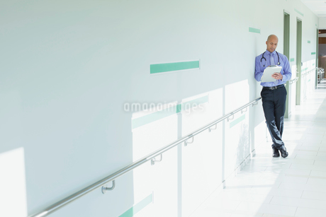 doctor reviewing chart in long hallwayの写真素材 [FYI02286470]