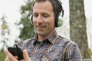 Mid-adult man listening to music on smartphone in the park.の写真素材 [FYI02286485]