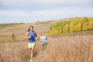 Two women running in field together.の写真素材 [FYI02286513]