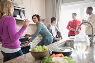 Group of friends gathered in domestic kitchen for dinner partyの写真素材 [FYI02286517]