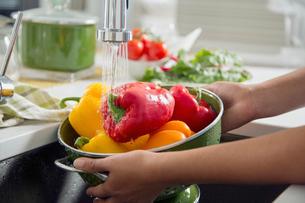 Women rinsing fresh peppers in the sink.の写真素材 [FYI02286534]