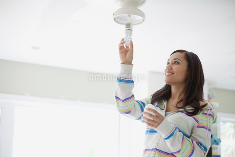 mid adult latino woman replacing light bulbの写真素材 [FYI02286580]