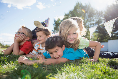 Young cousins piling up on each other outdoors.の写真素材 [FYI02286581]