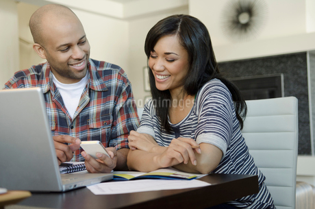 attractive couple working together on laptopの写真素材 [FYI02286605]