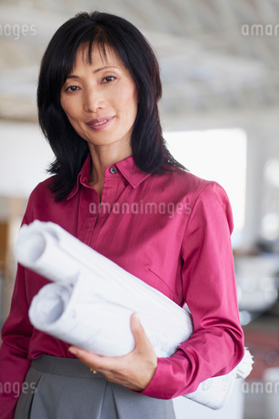 portrait of middle aged woman with blueprintsの写真素材 [FYI02286624]