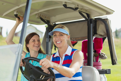 two female golfers laughing in golf cart togetherの写真素材 [FYI02286628]