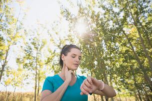 Woman stopping to check her heart rate during run.の写真素材 [FYI02286644]