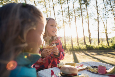 Sisters having dinner at an outdoor kids table.の写真素材 [FYI02286667]