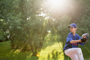 young male baseball pitcher winding up to throwの写真素材 [FYI02286672]