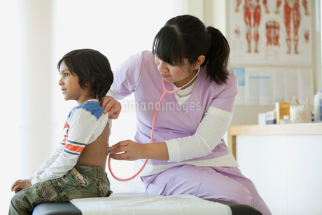 nurse checking young patient with stethescopeの写真素材 [FYI02286706]