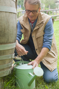 senior man filling watering can with water from a rain barrelの写真素材 [FYI02286715]
