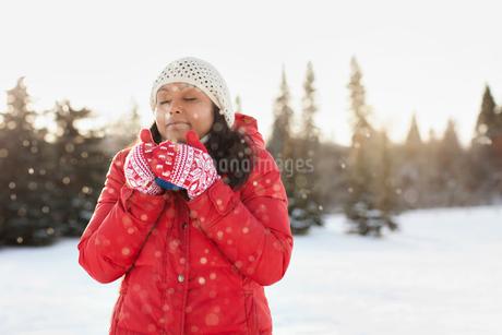 Woman enjoying hot drink in the snowの写真素材 [FYI02286724]