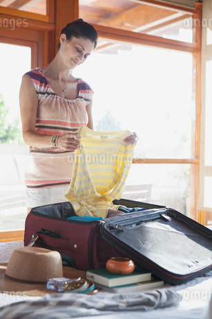mid adult woman unpacking suitcaseの写真素材 [FYI02286799]