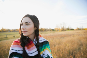 Pensive brunette young woman wrapped in a blanket in fieldの写真素材 [FYI02286868]